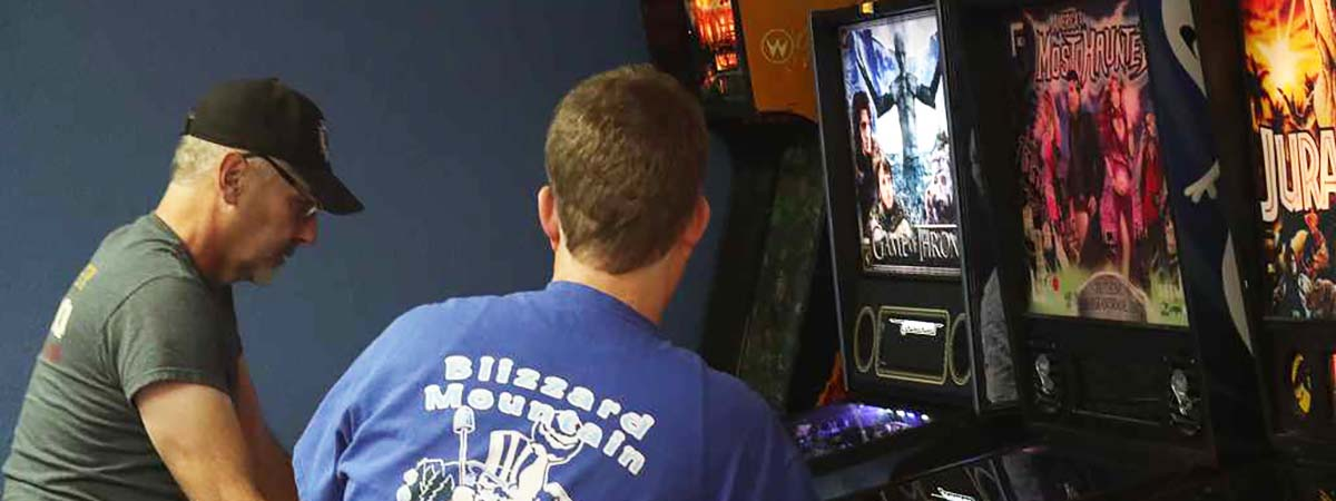 Header Our Games Page. Photo shows gentleman playing pinball and Blizzard staff member watching.