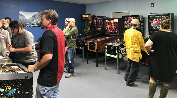 People playing pinball at a tournament